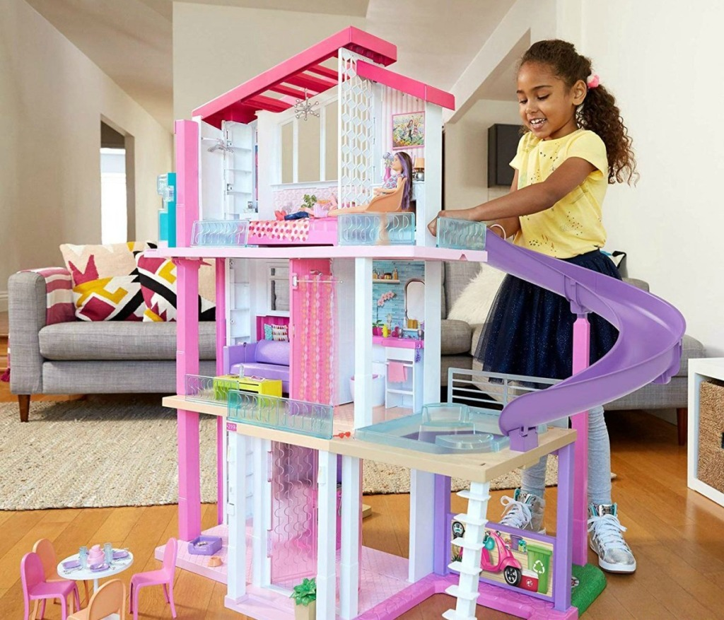 girl playing with Barbie dream house