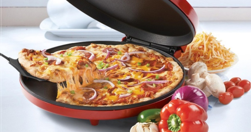 Betty Crocker Red Pizza Maker sitting on counter with vegetables