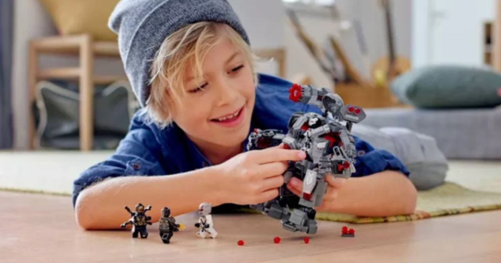 Little boy playing with LEGO Marvel Avengers War Machine Buster Set