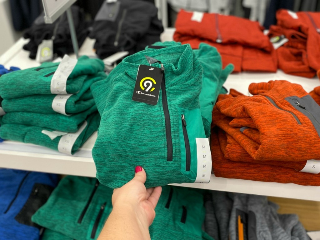 Hand holding green boys sweatshirt in Target near in-store display