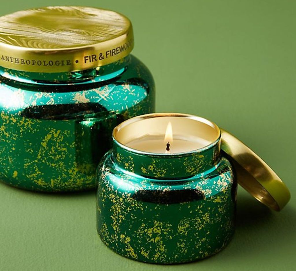 Capri Blue Fir & Firewood Jar Candle on green background with one candle lit