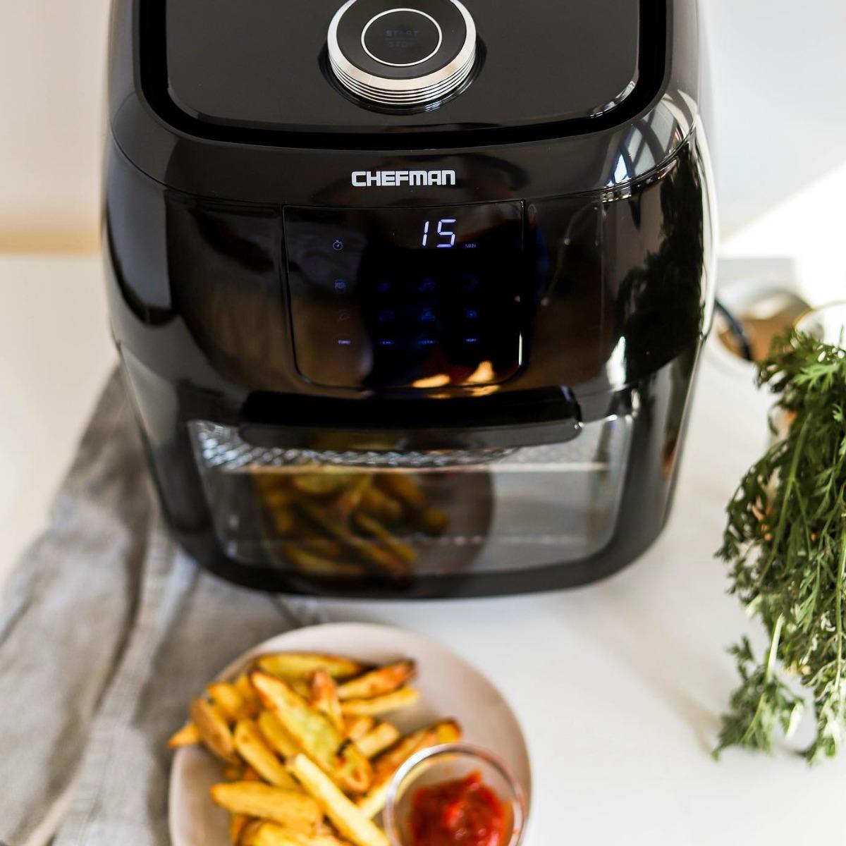Black digital air fryer near bowl of fries
