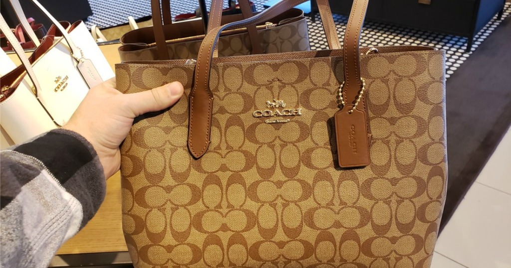 hand holding Coach Tote in a store