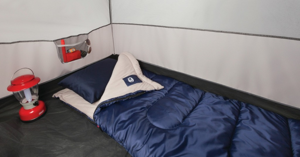 Coleman brand sleeping bag in navy blue on a tent floor near a lantern