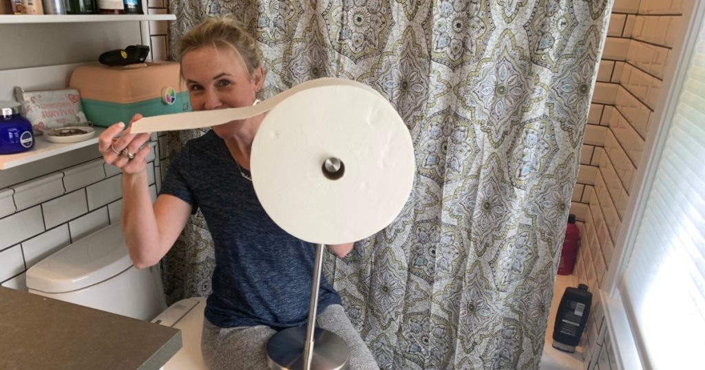 woman holding charmin forever roll in the bathroom on the toilet