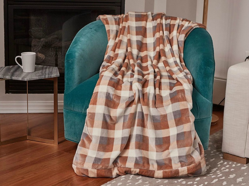 A Plaid Cuddl Duds Plush Velvet Foot Pocket Throw on a teal arm chair
