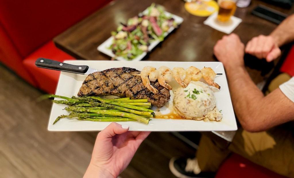 hand holding a steak dinner on plate