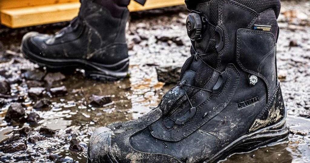 man wearing DeWalt work boots in the mud