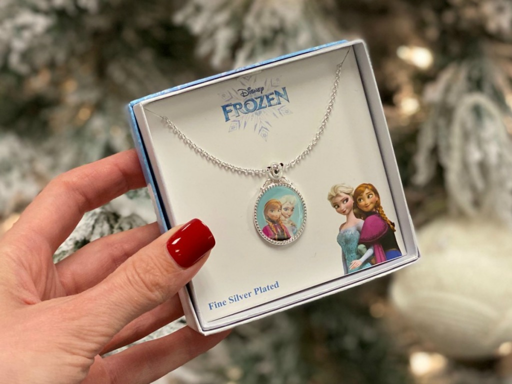 Disney Frozen 2 Sister Pendant in gift box in hand near Christmas tree