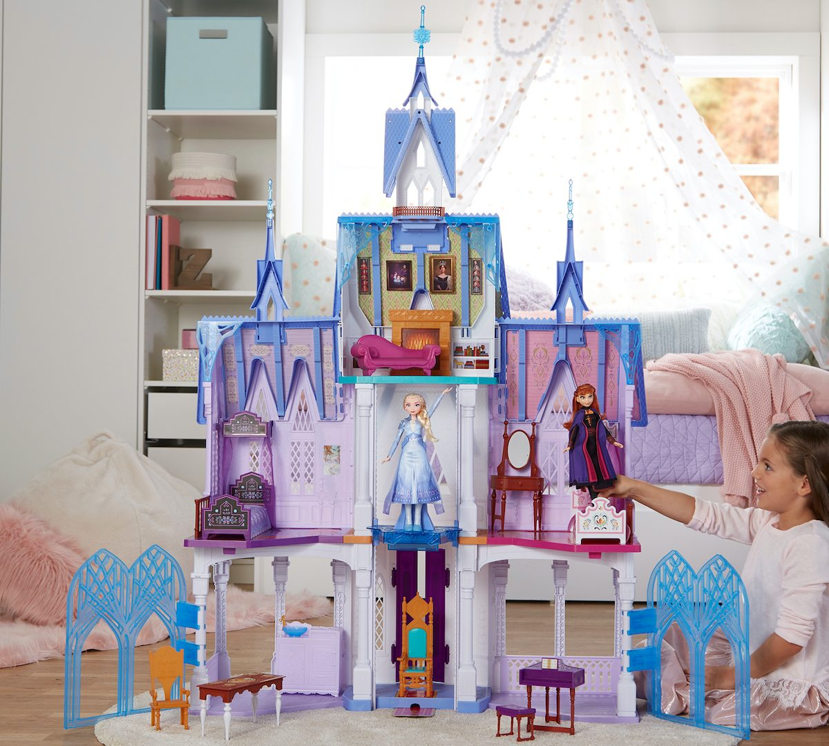 girl playing with Disney Frozen Ultimate Arendelle Castle in bedroom