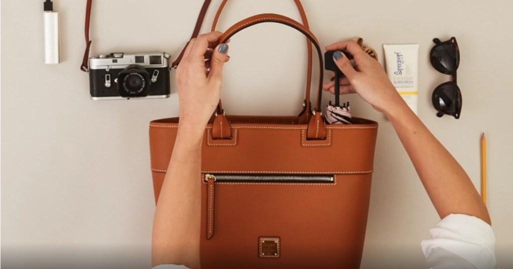 woman putting an umbrella in a brown purse