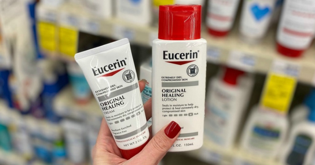 Woman holding two Eucerin healing products in hand near in-store display