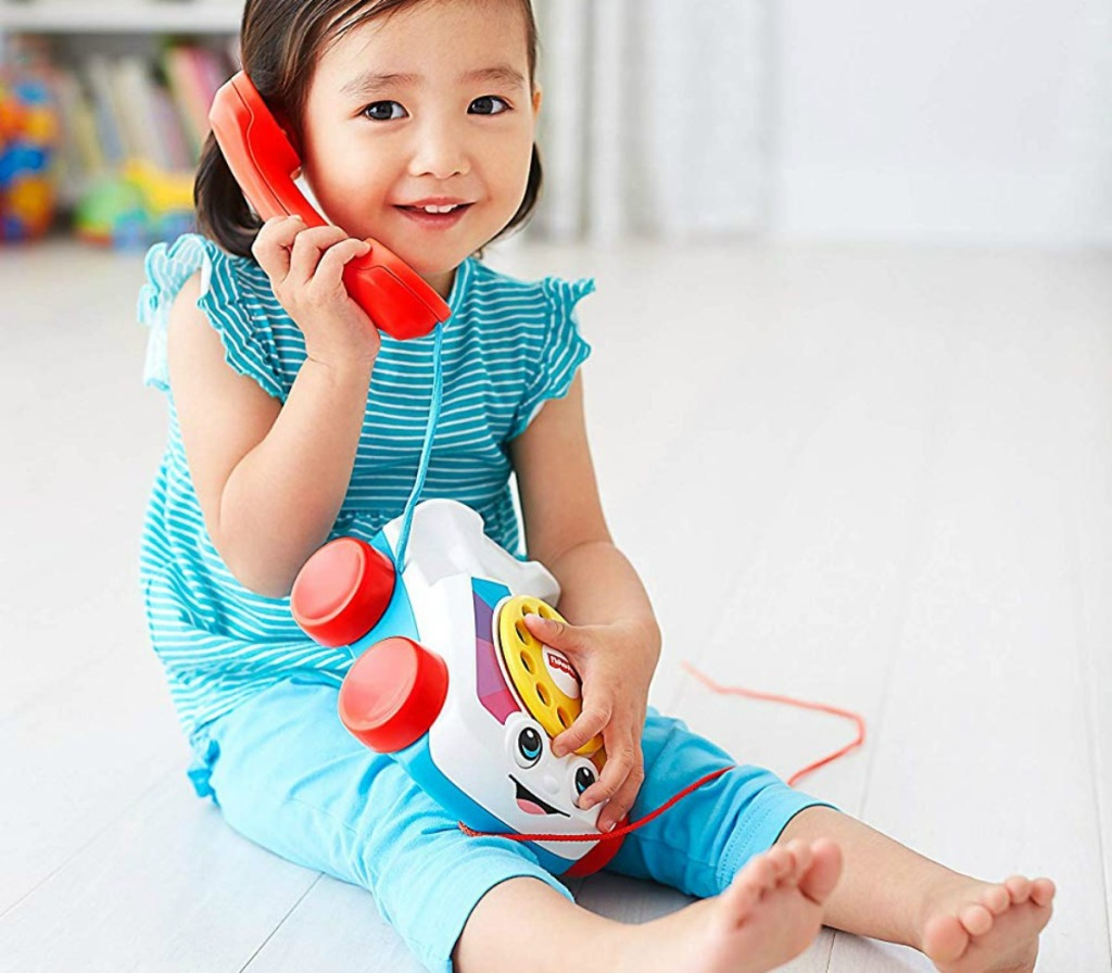 little girl playing with a Fisher-Price chatter telephone