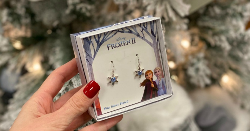 Frozen 2 themed earrings in gift box in hand in front of Christmas tree