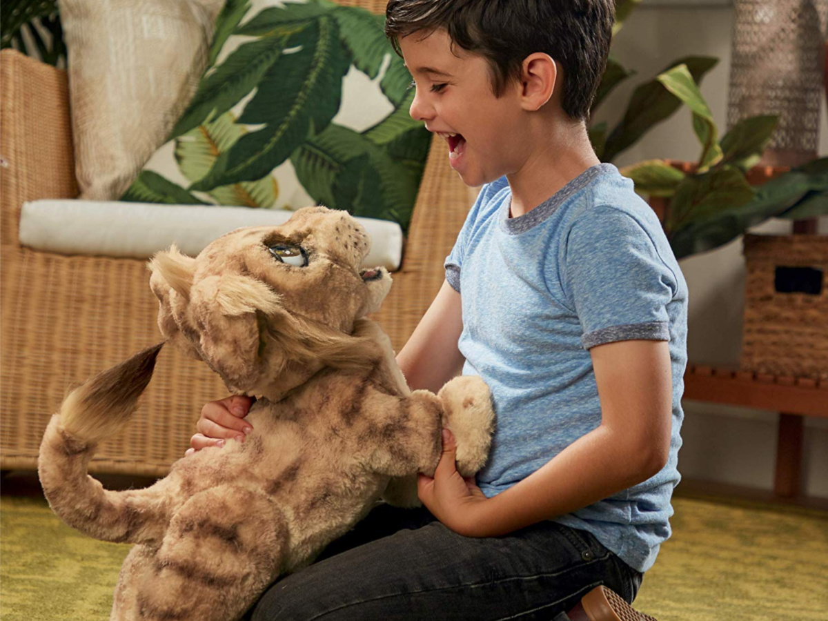 kid playing with interactive lion plush