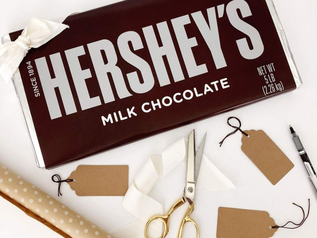 Giant hershey's 5 pound chocolate bar with gold scissors, gift tags, and wrapping paper
