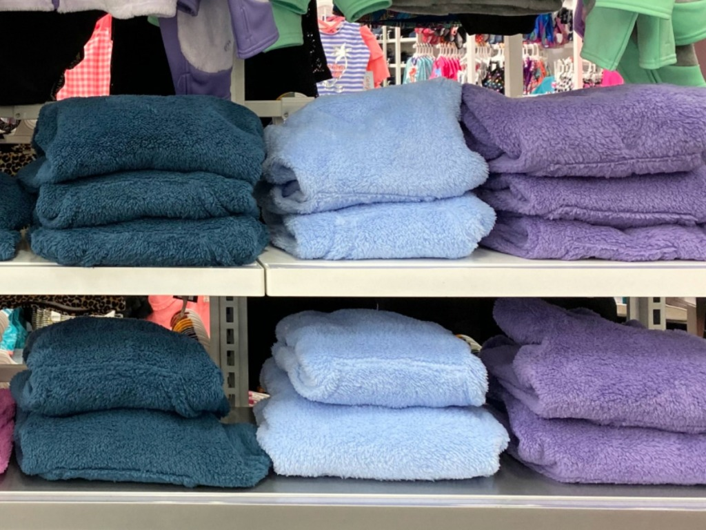 Girls sherpa hoodies folded and on display at Target