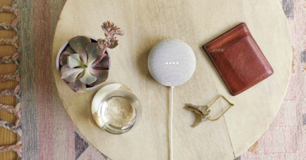 Google Nest Mini on table next to a glass of water, cactus, wallet and keys