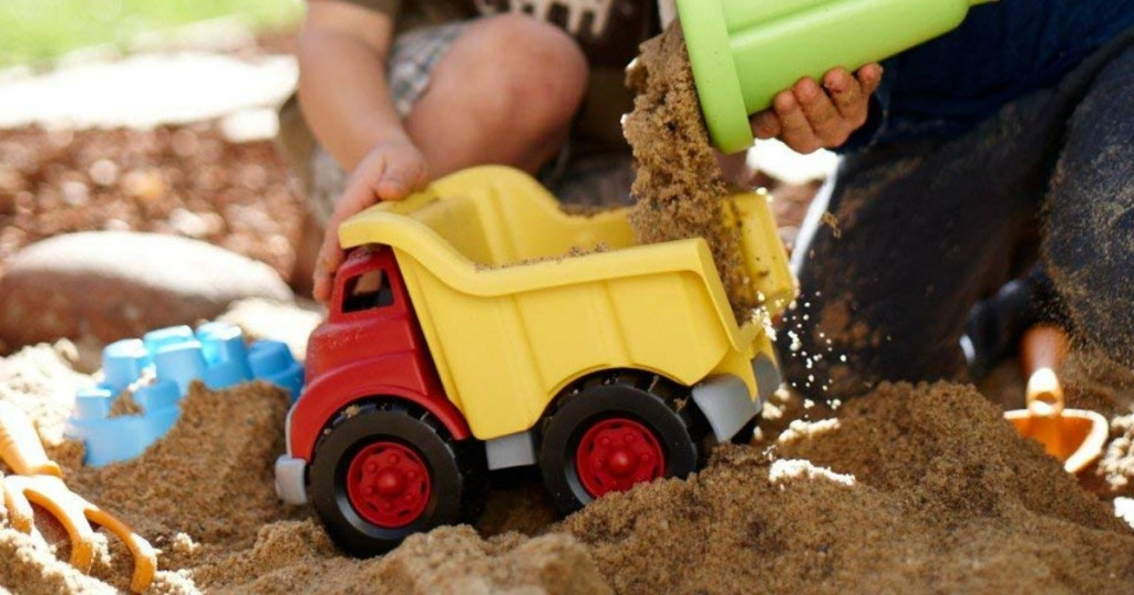 Boys playing in sand with Green Toys Dump Truck