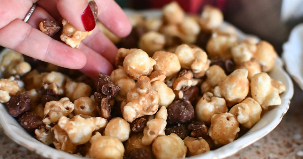 woman reaching for caramel popcorn and chocolate mix