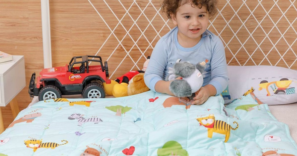 kid sitting on bed with toys and weighted blanket