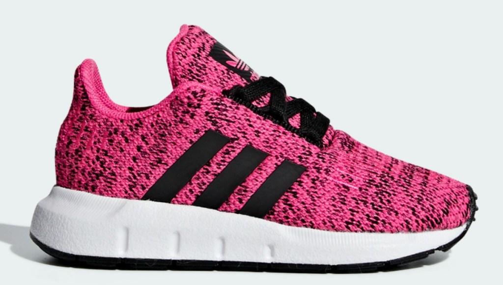 Pink kids shoe with black adidas stripes