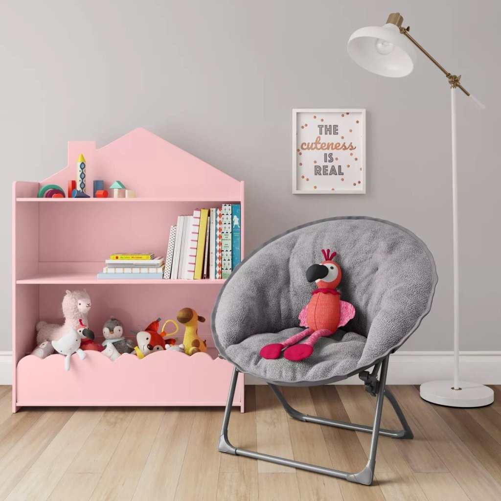 kids chair with a stuffed animal in it and a pink bookshelf
