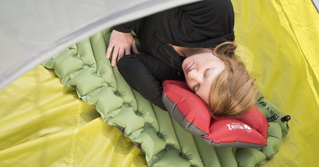 woman using sleeping pad in tent