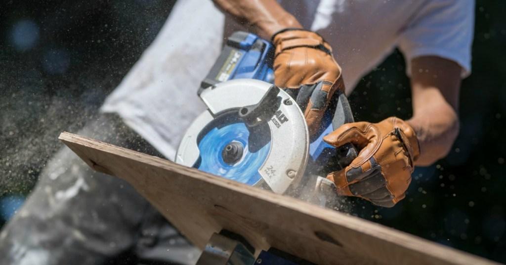 man using a Kobalt circular saw to cut plywood