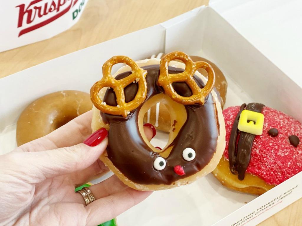 Krispy lady holding a Kreme Reindeer Doughnut