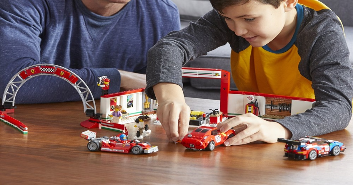 LEGO Speed Champions Ferarri set, put together on a table, son playing with it as father sits next to him at a table