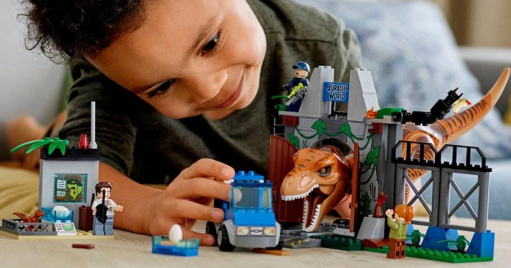 boy palying with jurassic world lego set