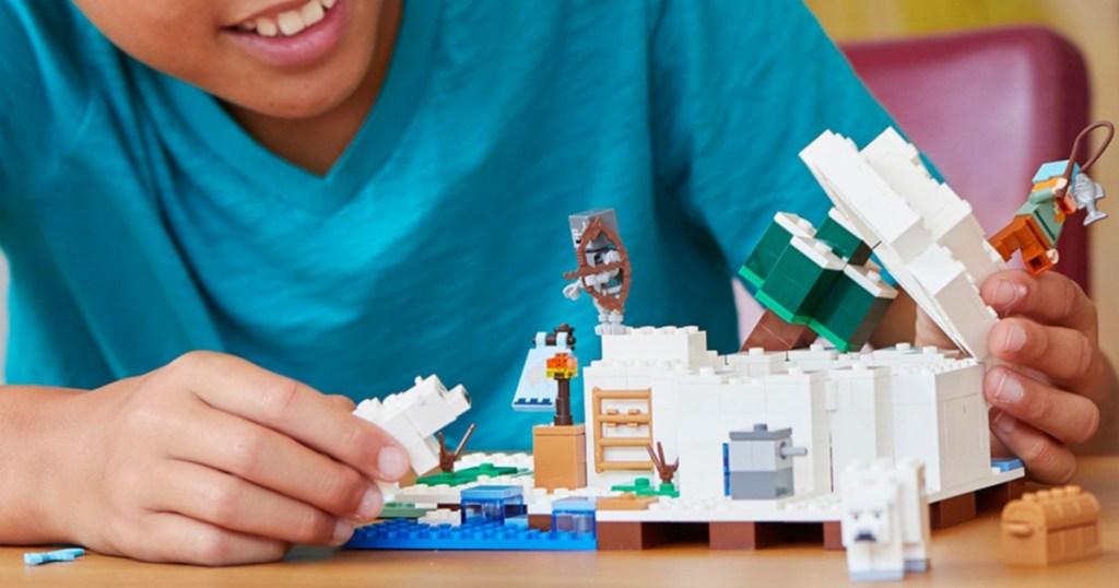 boy playing with minecraft lego set