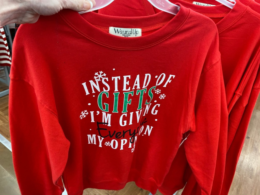 hand holding red holiday sweatshirt