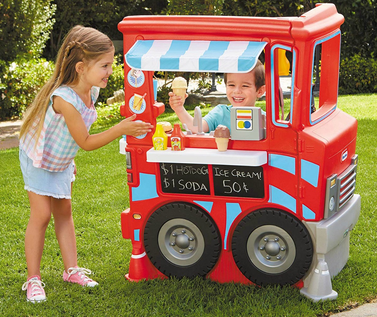 Kids playing with a Little Tikes 2-in-1 food truck outside