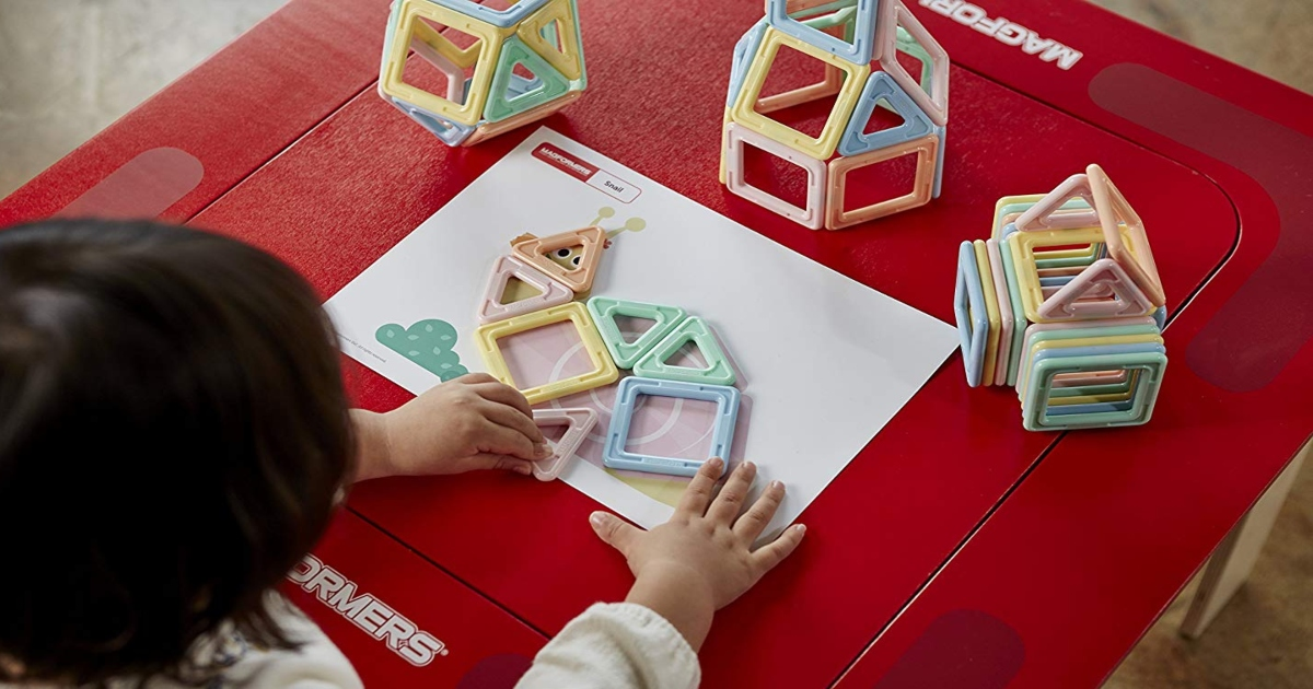 Child sitting at a red table, playing with Pastel Magformers