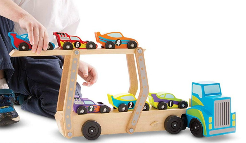 Boy playing with a wooden race care carrier truck