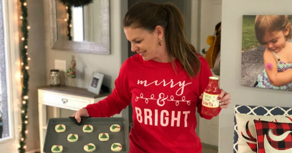 woman holding Christmas cookies and milk for Santa glass wearing Merry & Bright shirt