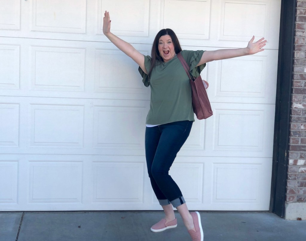 woman with hands in the air standing in front of white garage door