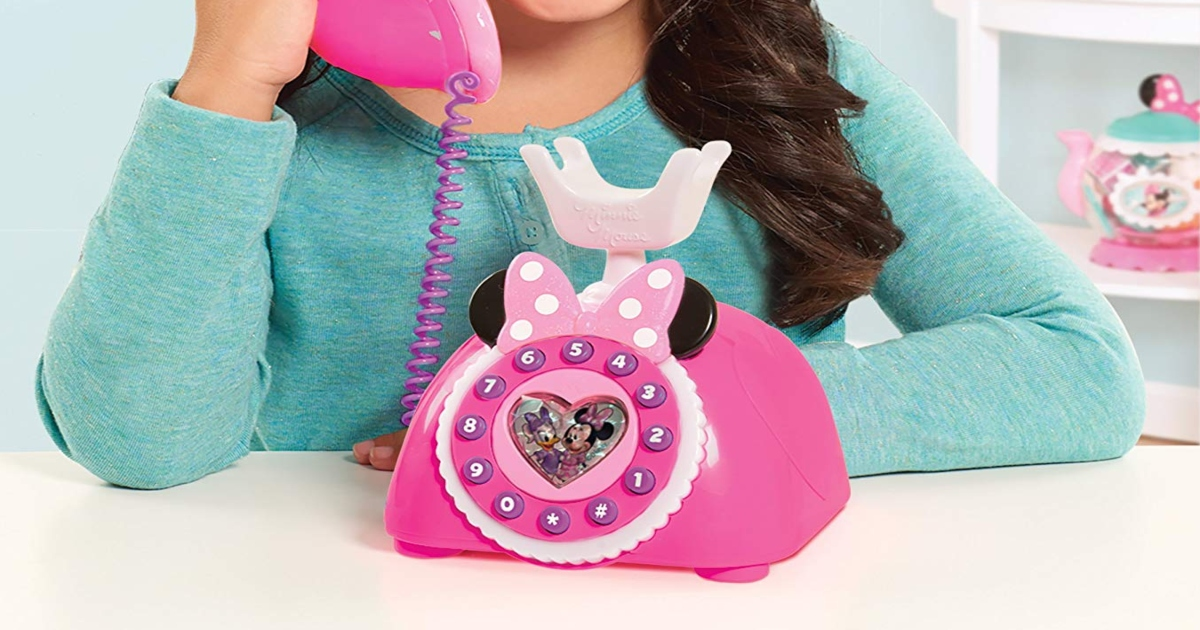 Girl in teal shirt answering a pink Minnie Mouse Phone