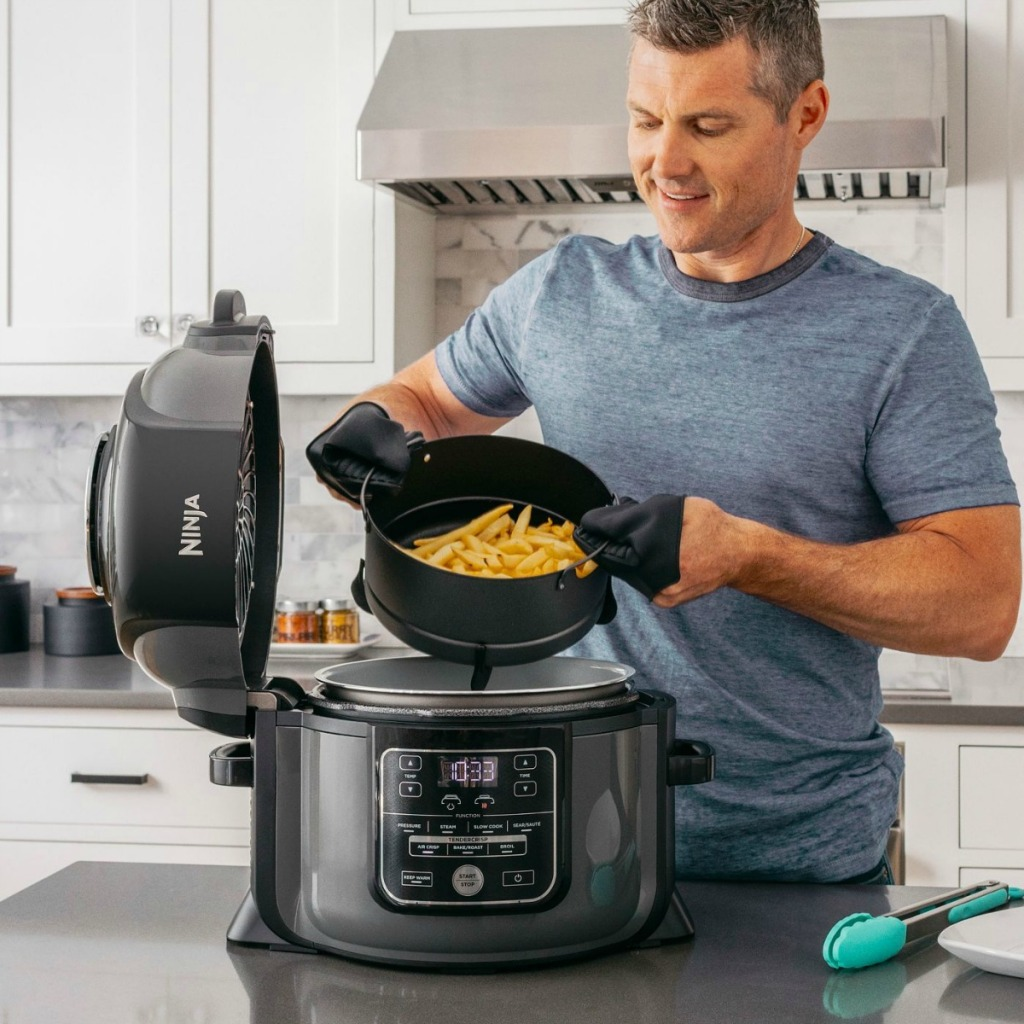man removing a pan of fries from an air fryer
