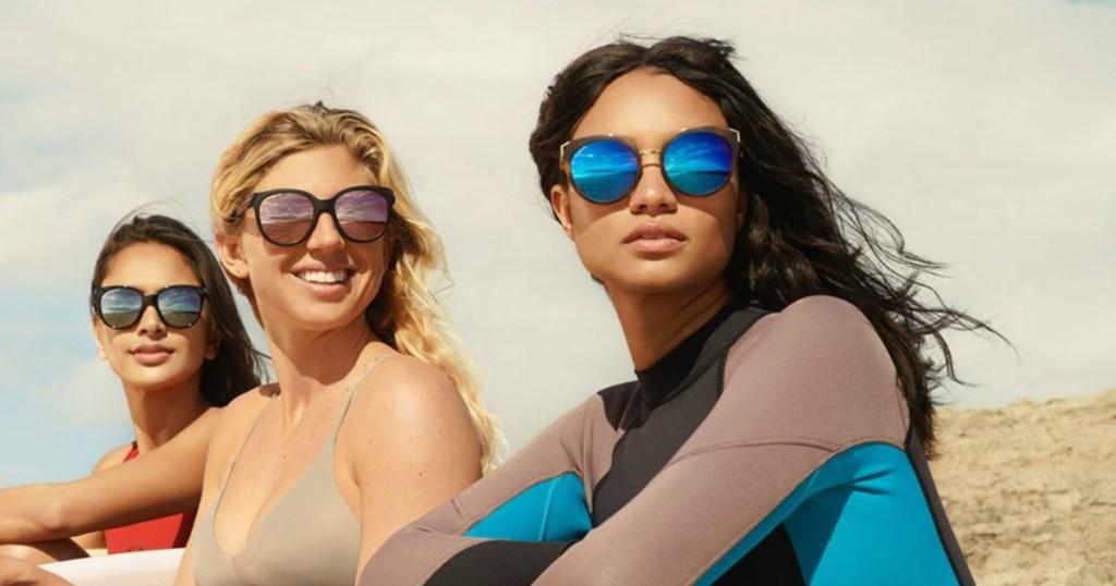 three women at the beach wearing swimwear and sunglasses