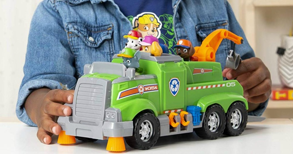 boy playing with a Paw Patrol green rescue truck