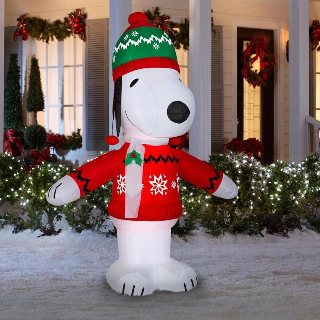 Peanuts Lighted Snoopy Christmas Inflatable in snowy yard in front of house