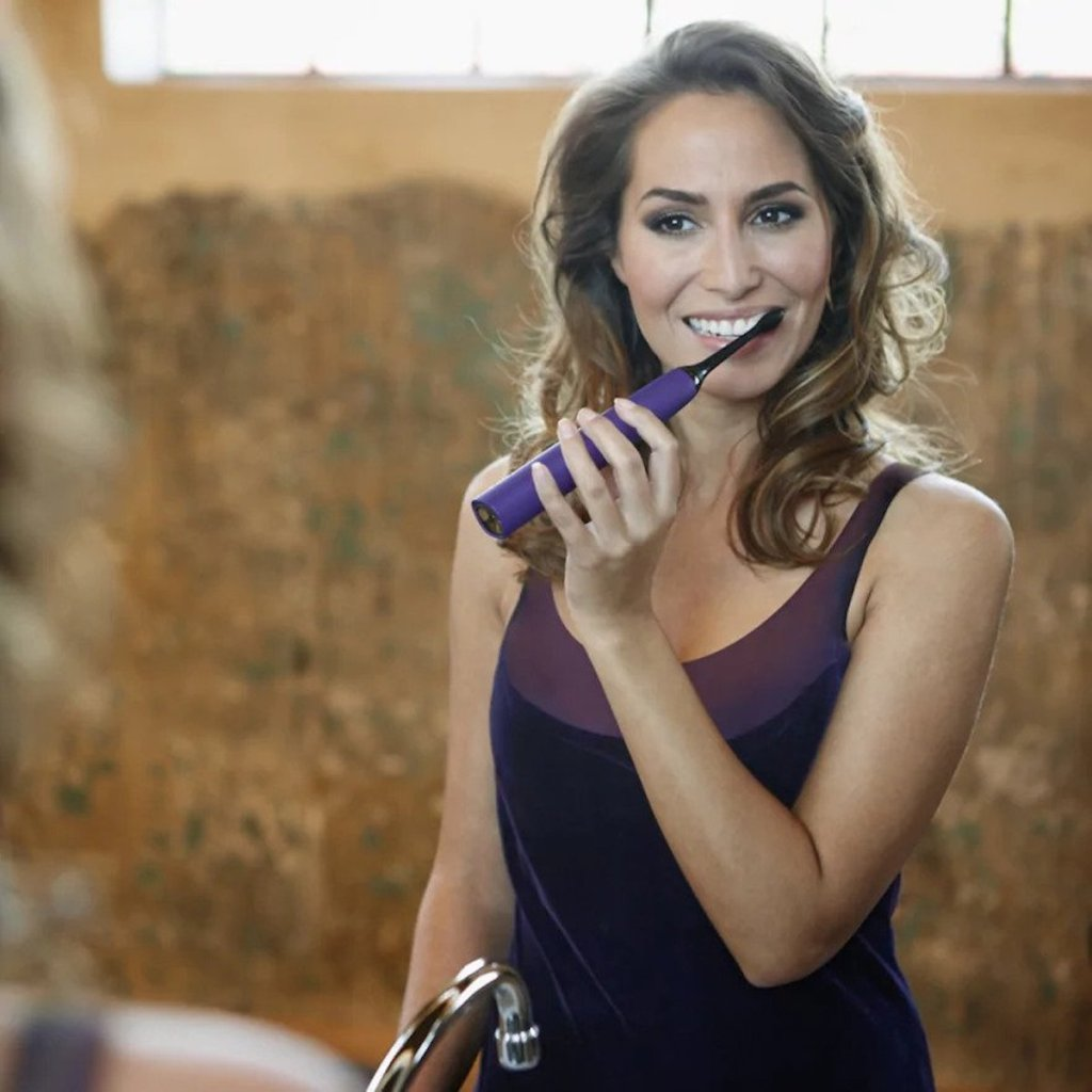 woman brushing her teeth in bathroom with Philips Sonicare DiamondClean In Purple