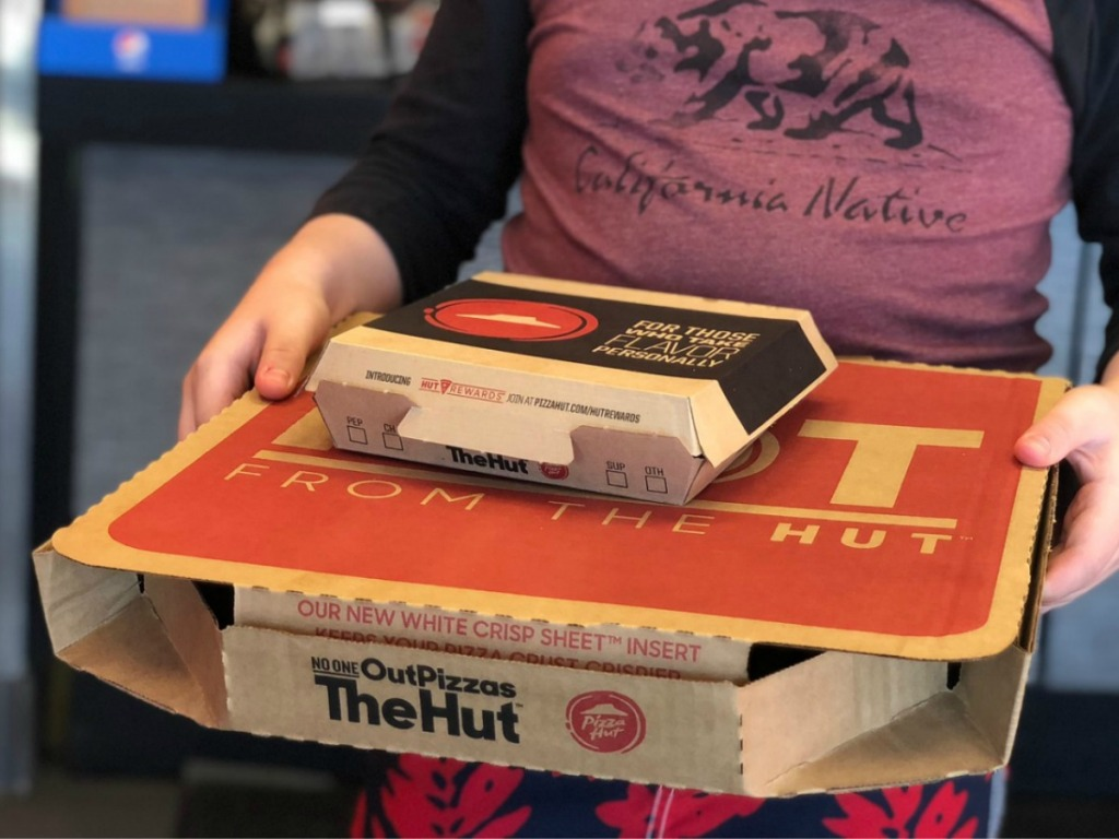 person carrying two pizza boxes from Pizza Hut