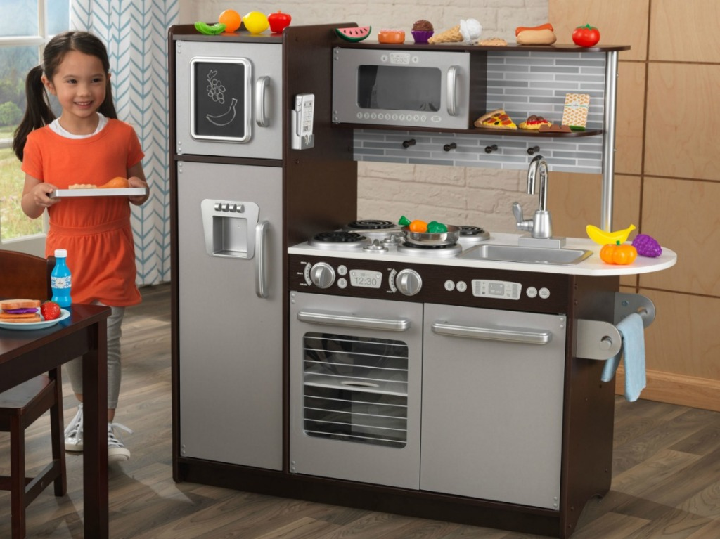Young girl playing with a toy kitchen and play food