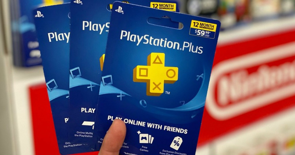 someone holding three playstation plus gift cards