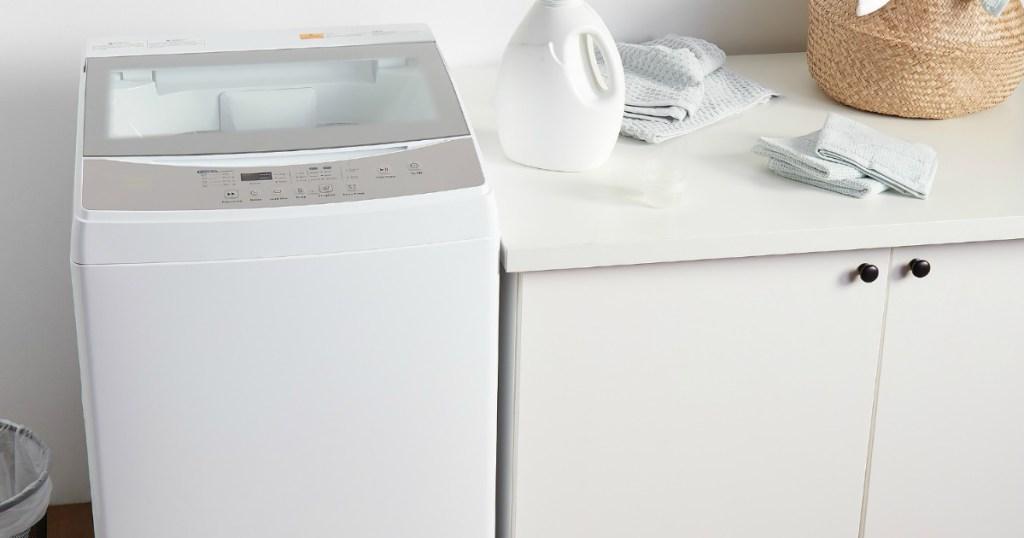 small washing machine next to a cabinet