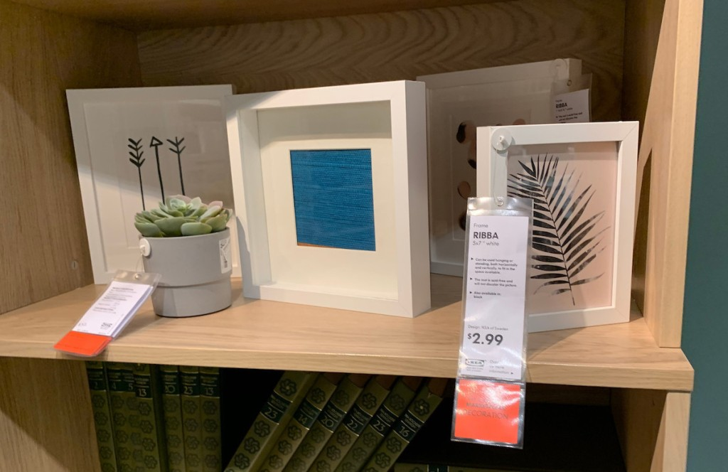 various sizes of square white picture frames sitting on wood bookshelf